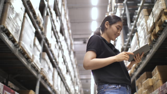 asian woman checking supplies on digital tablet in the warehouse - distribution warehouse stock videos & royalty-free footage