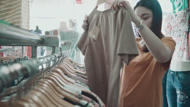 asian woman chooses clothes at shopping mall - klänning bildbanksvideor och videomaterial från bakom kulisserna