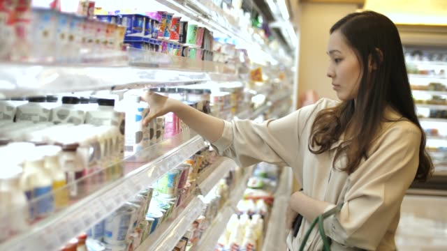 asian woman chooses milk in the supermarket - fare spese video stock e b–roll