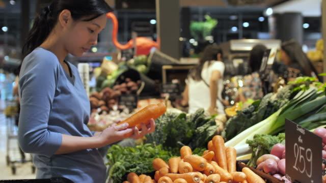 アジアの女性は、スーパーマーケットで野菜を選択します - 野菜点の映像素材/bロール