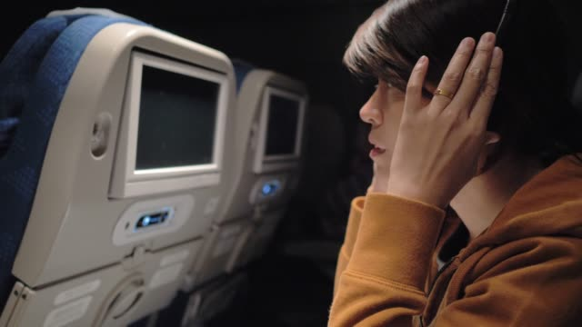asiatisk kvinna att välja och lyssna på musik på smart telefon i planet. - konstkultur och underhållning bildbanksvideor och videomaterial från bakom kulisserna