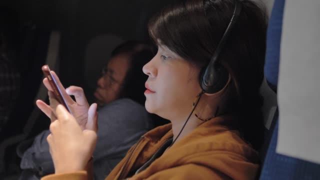 vídeos de stock, filmes e b-roll de mulher asiática que escolhe e que escuta a música no telefone esperto no plano. - smart