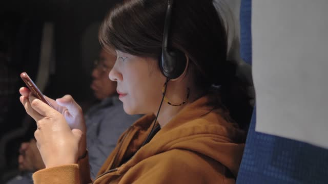 Asian woman choosing and listening music on smart phone in the plane.