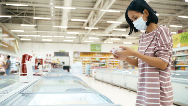 asian woman choosing and picking frozen food from refrigerator in supermarket store with face mask protection from corona virus and flu for healthy. - frozen food stock videos & royalty-free footage