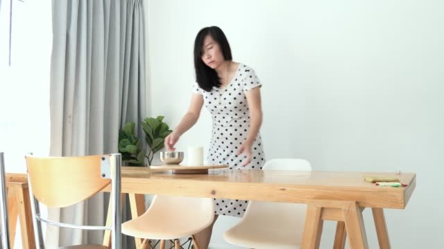asian woman cleaning and watering indoor plant near window at home, lifestyle concept. - one mature woman only stock videos & royalty-free footage