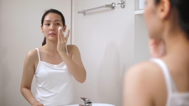 vídeos de stock, filmes e b-roll de mulher asiática limpando rosto no banheiro em casa - chuveiro instalação doméstica