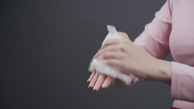 vídeos de stock, filmes e b-roll de mulher asiática limpando as mãos sujas com papel de limpeza de bebê. mulher adulta usando tecido branco molhado para limpar a mão. saúde, conceito de higiene e beleza em fundo cinza com espaço de cópia. fechar - molhado