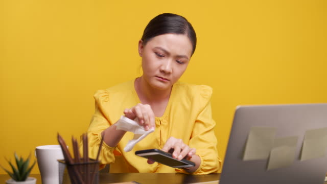 asian woman cleaning smart phone and laptop over yellow background - tessuto umano video stock e b–roll