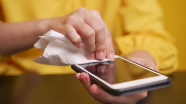 asian woman cleaning smart phone over yellow background - tessuto umano video stock e b–roll
