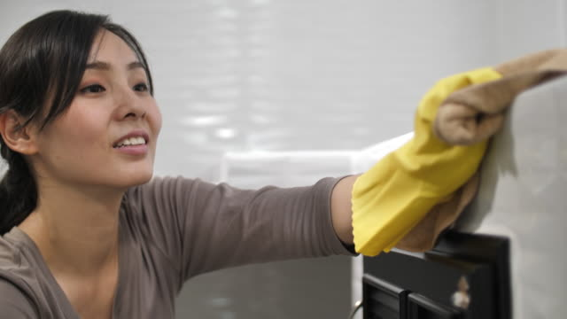 asian woman cleaning untidy kitchen - spray cleaner stock videos & royalty-free footage
