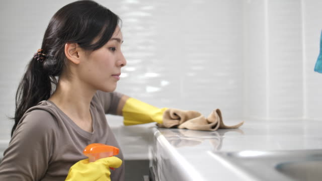 asian woman cleaning untidy kitchen - rubber glove stock videos & royalty-free footage