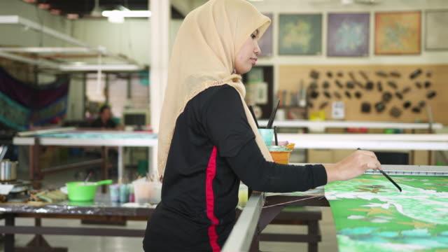 asian woman colouring the patterns on batik - batik stock videos & royalty-free footage