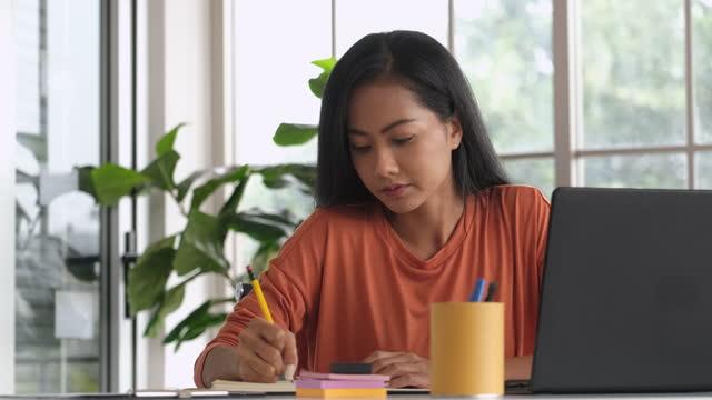asiatische frau content creator schreiben von inhalten auf notebook und arbeiten von zu hause.planung marketing, projektplan auf planer - content stock-videos und b-roll-filmmaterial