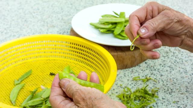 vídeos y material grabado en eventos de stock de mujer asiática en la cocina a la vista al jardín - utensilio para cocinar