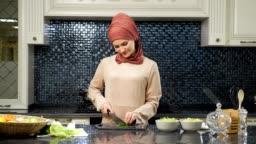 oriental woman cooks meal cutting fresh greens smiling