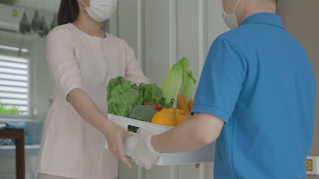 vídeos de stock, filmes e b-roll de mulher asiática fantasiando máscara facial recebe caixa de alimentos, frutas e legumes do entregador em frente à casa durante o tempo de isolamento doméstico. - receber