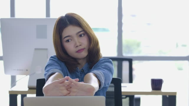 stockvideo's en b-roll-footage met creatieve ontwerper aziatische vrouw die op laptop werkt en strekken van de armen omhoog op bureau in moderne kantoor. - strekken