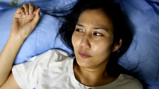asian woman crying on bed