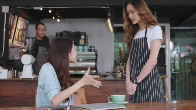asian woman customer complaining to waitress about food in cafe restaurant, unhappy customer service in coffee shop - delusione video stock e b–roll