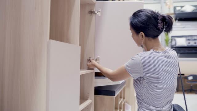 アジアの女性の顧客の買い物と家の装飾のためのテーブルと本棚の木材を選択します。ショッピングストアでハードウェアや家具を購入アジアの女性。 - 貯蔵庫点の映像素材/bロール