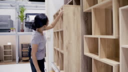 Asian woman customer shopping and choosing Table and Book Shelf wood for home decoration. Asian female buying hardware and furniture at shopping store.