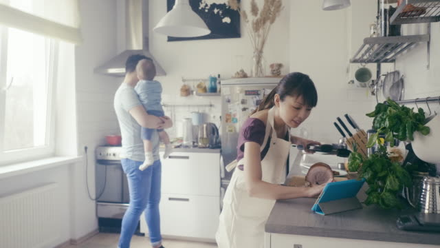 asian woman cuts pork and uses digital tablet as a cookbook - studio camera video stock e b–roll