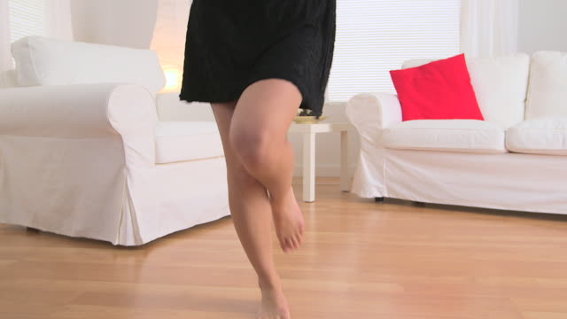 Asian woman dancing in living room
