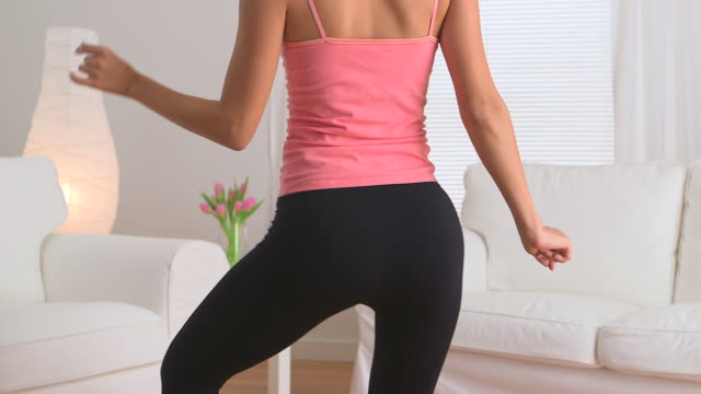 Asian woman dancing in yoga pants