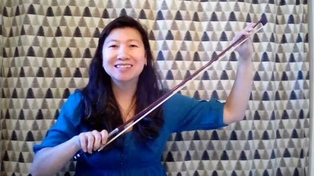 vídeos de stock, filmes e b-roll de asian woman demonstrates how to properly play the violin for an online audience. (audio) - câmera de conferência