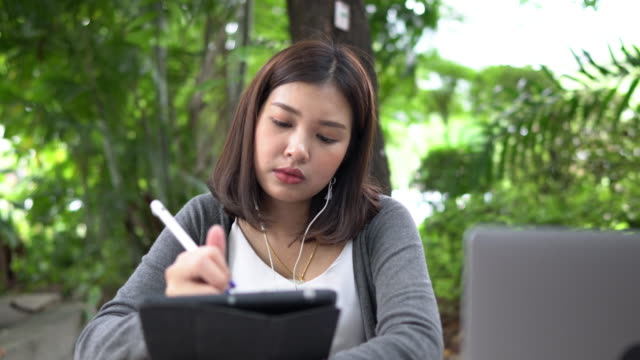 asian woman designer using digital pen to draw on graphic tablet and listening music relaxedly in park of university, pan shot - digitized pen stock videos & royalty-free footage