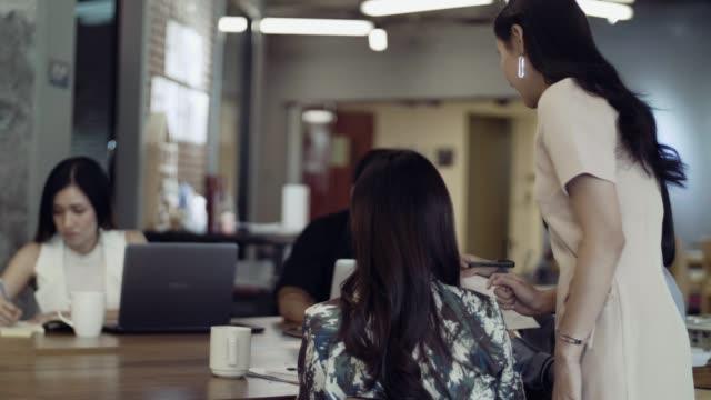 vídeos de stock e filmes b-roll de asian woman discussing new business strategy with team - focagem