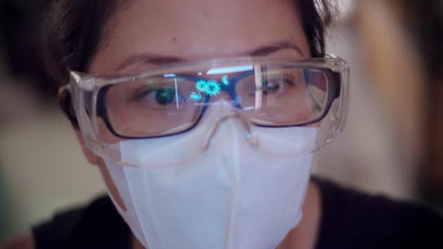vídeos y material grabado en eventos de stock de mujer asiática doctora con máscara y gafas buscando coronavirus imagen de datos en el ordenador. - patólogo