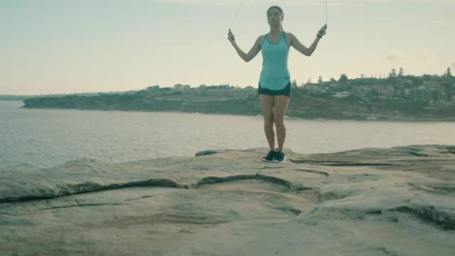 vídeos de stock e filmes b-roll de asian woman does jumping rope exercise (slow motion) - corda de saltar
