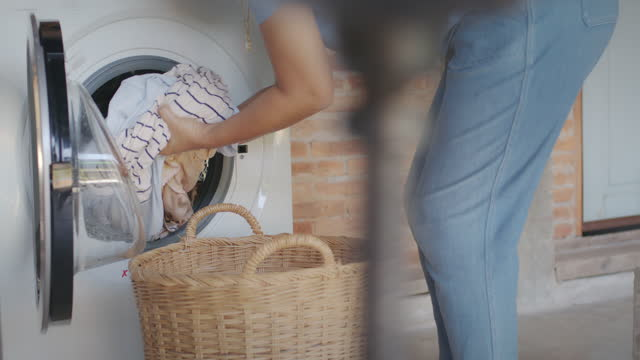 asian woman doing chores. woman hand taking clothes out from washing machine drum after finished washing for drying at home. - tumble dryer stock videos & royalty-free footage