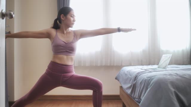 vídeos y material grabado en eventos de stock de mujer asiática haciendo ejercicio de yoga en el dormitorio - vriksha asana