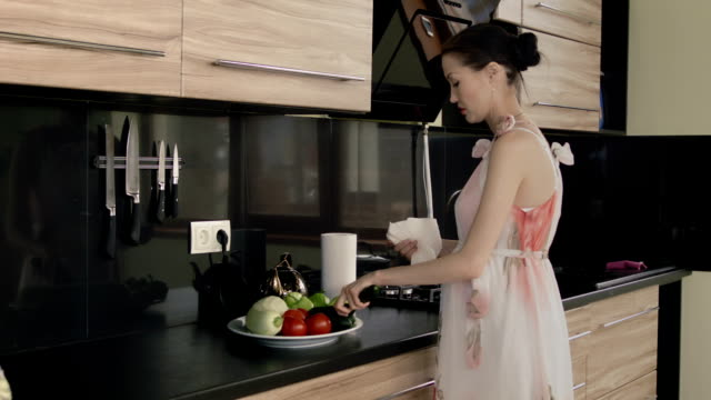 Asian woman dries vegetables in the kitchen