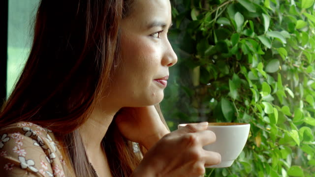 Asian woman drink coffee and looking Through window