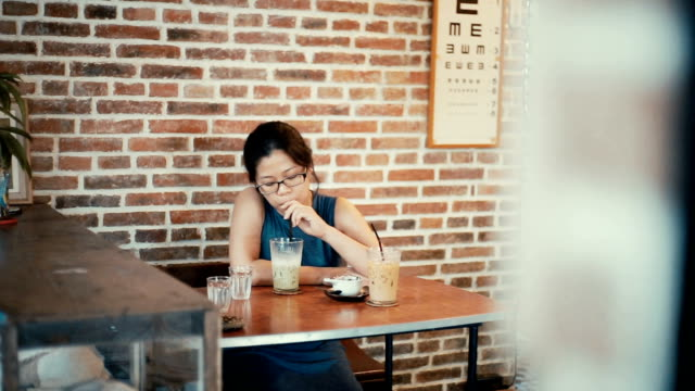 asian woman drinking iced green tea latte in a coffee shop. - brick wall stock videos & royalty-free footage