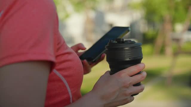 vídeos y material grabado en eventos de stock de mujer asiática bebiendo botella reutilizable en el parque - three quarter length