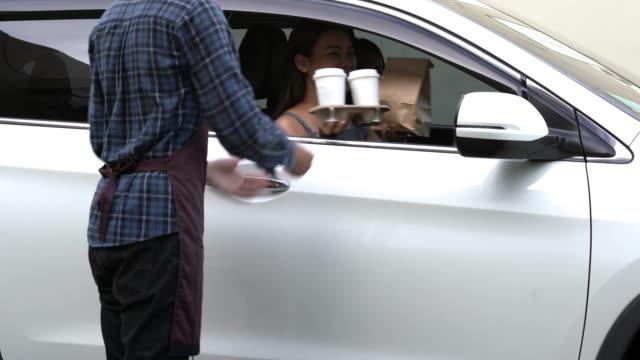 vídeos y material grabado en eventos de stock de mujer asiática conducir coche y recoger la comida y el café de empleado a través de la unidad a través de la estación de restaurante - fast food