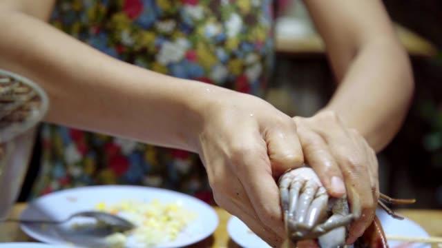 アジアの女性はカニシーフードグリルバーベキューを食べる。 - カニ捕り点の映像素材/bロール