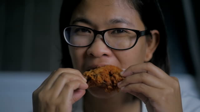 Asian woman eating fried chicken, Slow motion
