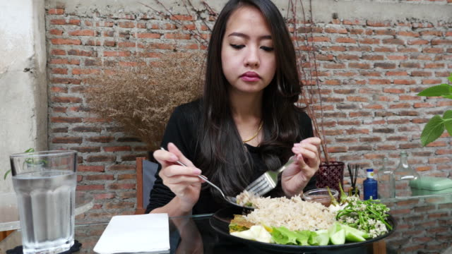 asian woman eating fried rice - fried rice stock videos and b-roll footage