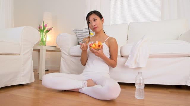 Asian woman eating fruit bowl