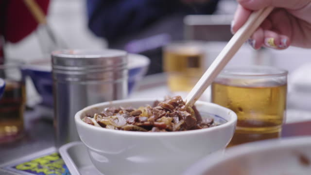 vídeos de stock e filmes b-roll de asian woman eating gyudon, a japanese cuisine, japanese rice topped with sliced grilled beef - pauzinhos