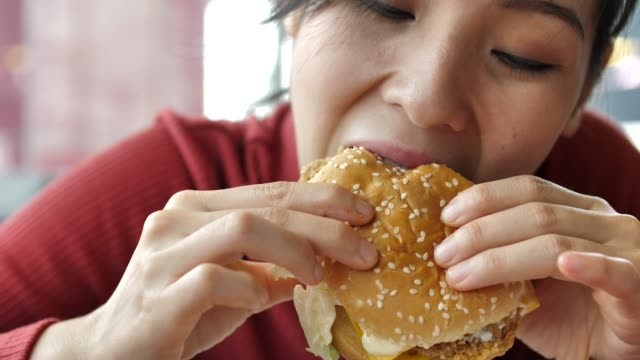 stockvideo's en b-roll-footage met aziatische vrouw eten hamburger - unhealthy eating