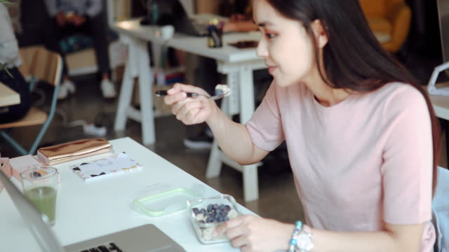 asian woman eating healthy breakfast at office - healthy eating stock videos & royalty-free footage