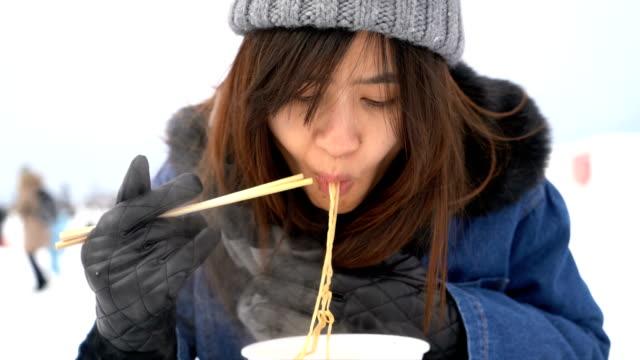 冬の雪でアジアの女性 eeating インスタント ラーメン - 高級グルメ点の映像素材/bロール