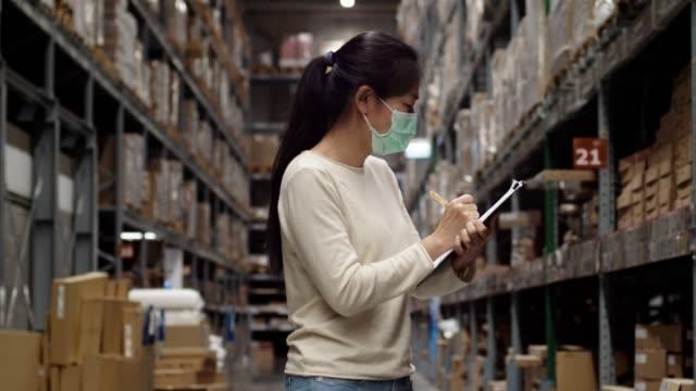 アジアの女性従業員または監査役スタッフは、倉庫の在庫残高をカウントしてチェックしています。 - 棚点の映像素材/bロール