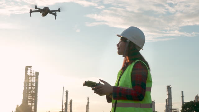 asian woman engineer operate flying drone over oil refinery plant during sunrise building site survey in civil engineering project. - building activity stock videos & royalty-free footage